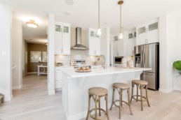 Daytona Homes Showhome, white kitchen in Jensen Lakes with modern accents. View showhome hours.