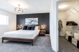 Main bedroom with walk in closet, grey accent wall and wood side tables modern classy design. Daytona Homes Austyn Jensen Lakes St .Albert