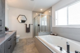 Bathroom with grey wood cupboards and brown tiles, glass shower with large tub. Showhomes by Daytona Homes in Jensen Lakes St. Albert