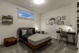 Bedroom with grey bed walls and chair modern wall decor and wood bedfame. Jensen Lakes Showhome