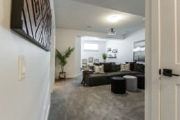 Basement den with black and grey couch space, grey walls and plan accent decorations. Jensen Lakes Daytona Homes.