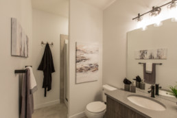 Bathroom with grey counter and black faucet, white walls and white and black wall decorations. Jensen Lakes Austyn Showhome in St. Albert