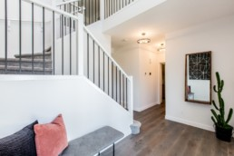 White trimmed staircase with grey wire leading to main hardwood brown floor with plant. Jensen Lakes showhome St. Albert
