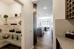 Separated pantry with white wire shelves leading hallway to kitchen. Austyn showhome Jensen Lakes St. Albert
