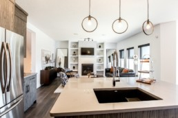 Kitchen with ring style light fixture, white countertops and grey wood patterned cupboards, connected to open living room with black and white chairs and couches with orange accent pillows and large windows. Jensen Lakes Daytona Austyn showhome in St. Albert