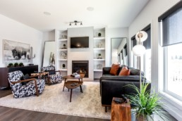 Open living room with black leather couch and orange pillows, black and white geometric patterned chairs and silver statement pieces alongside tv with large windows. Jensen Lakes Daytona Showhomes.