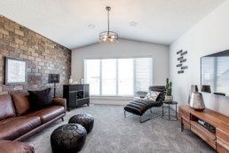 Upstairs bonus room with brown brick wall, brown and black leather furniture and wooden tv stand. Austyn Daytona Showhome in Jensen Lakes community St. Albert