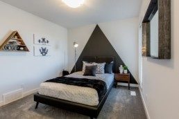 Bedroom with black and grey modern design and triangle wall decals. Showhome in Jensen Lakes St. Albert.