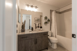 Bathroom with dark grey wood cabinets and dark faucets with geometric wall decorations. Austyn Showhome Daytona Homes Jensen Lakes.