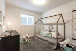 Childrren's room with wood dimesional frame bed, light blue design accents and beige walls. Jensen Lakes.