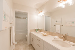 Bathroom with two sinks and separated shower and toilet. Gold faucets and beige tile. Located in Jensen Lakes.