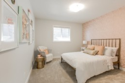 Bedroom with pink patterened wall and white bed sheets. Everest showhome St. Albert/