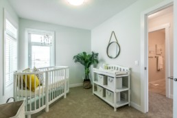 Nursery room with white crib and table, high windows and light green walls. Everest showhome Jensen Lakes.