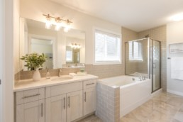 Ensuite bathroom with beige tile. Glass shower and white tub. Light wood cupboards and steel faucets. In Everest Showhome in Jensen Lakes.