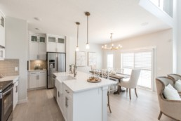 Kitchen with white countertops and light brown hardwood floor white chairs with dark wood accents. Located in Everest showhome Jensen Lakes