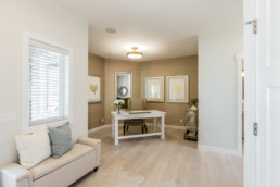 Home office with beige accent walls, hardwood floor and white desk, in Jensen Lakes St. Albert