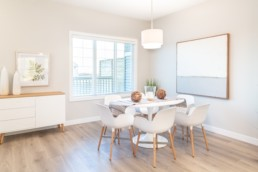 Dining area with white chairs and wooden chair legs. Beach modern design with white accents. Jensen Lakes St. Albert.