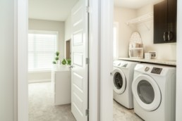 Laundry room with wooden cupboards for organization and spacious living in Jensen Lakes St. Albert.