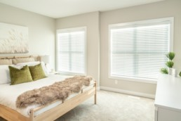 Main bedroom with big windows and light wood furniture in Jensen Lakes Showhome