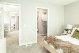 Jensen lakes show home bedroom with walk in closet and spacious hallway.