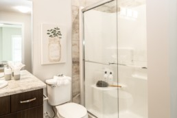 Showhome bathroom with beige décor and brown wood cupboards in Jensen Lakes.