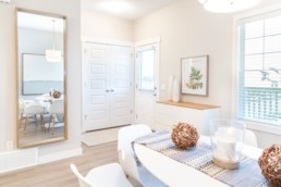 Atlas showhome St. Albert entryway. White and light wood chairs with modern beach home design.