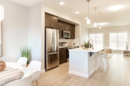 Showhome kitchen with dark brown wood ceiling high cupboards, stainless steel accents and white counters with white bar stools. Community of Jensen Lakes St. Albert.