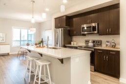 Kitchen with dark brown wood cupboards and white countertops. Atlas Showhome St. Albert.