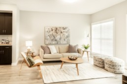 Jensen Lakes Atlas showhome living room with biege couches and neutral coloured modern beach decorations.