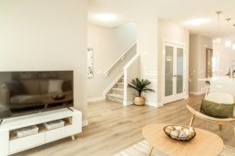 Atlas showhome in St. Albert TV area with wood coffee table and beach interior design, wood floors and white walls.