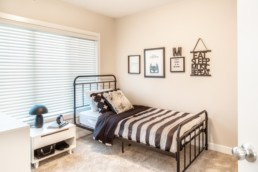 Showhome bedroom with wire black bed frame and black and white interior decor in Jensen Lakes Community in St. Albert