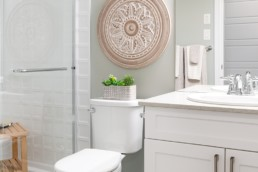Basement bathroom with white cabinets and separated glass shower with white tile. Pacesetter Showhome in Jensen Lakes