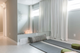 Show home basement gym ideas with yoga matts and pillows with mandala wall decorations and a zen art. The Lazzaro showhome by Pacesetter Homes in Jensen Lakes community in St. Albert