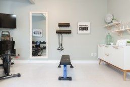 Home gym with stationary bike, weights bench and tv, spacious for organization and exercise. Pacesetter homes in Jensen Lakes St. Albert