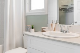 Ensuite bathroom with white cabinets and silver faucets. Showhomes in Jensen Lakes St. Albert