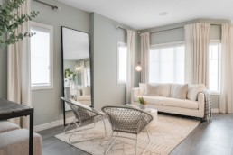 Great Room with wicker chairs and white couch, woven area rug and beige curtains. The Lazzaro Showhome by Pacesetter Homes in Jensen Lakes St. Albert