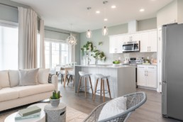Pacesetter Homes The Lazzaro Showhome in Jensen Lakes. White cabinets and white with wood barstools kitchen connected to great room..