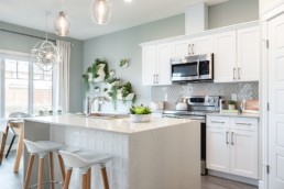 The Lazzaro by Pacesetter homes kitchen with white countertops glass light fixtures white with silver cupboards and light wood with white stools on hardwood flooring in Jensen Lakes St. Albert