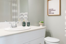 Main bathroom with white countertops and neutral grey walls. Showhomes in Jensen Lakes St. Albert