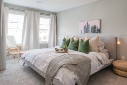 Owners Suite with green and grey pillows and wicker side table. The Lazzaro by Pacesetter Homes in Jensen Lakes St. Albert