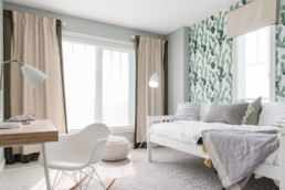 Secondary bedroom with cacti wallpaper and wooden desk, white chair and bed decor. Pacesetter showhomes in Jensen Lakes