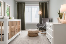 Secondary bedroom nursery with wicker furniture, white cabinet and white with light toned wood crib with dark green curtains in Jensen Lakes St. Albert