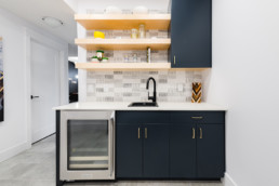 Basement bar with navy blue cabinets and gold accents, mini fridge and wood shelves. The Lusitano Showhome basement in Jensen Lakes St. Albert