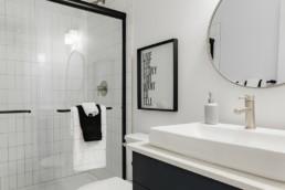 Basement bathroom with navy cabinets and black trimmed glass door shower. Jensen Lakes St. Albert