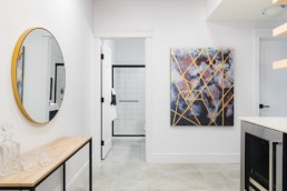 The lusitano showhome basement area with gold laced art and mirror located in Jensen Lakes showhomes