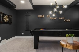 Basement recreation room with pool table and black walls, art decals and dart board. Jensen Lakes Showhomes in St. Albert by Pacesetter Homes