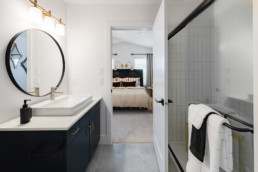 The Lusitano showhome by Pacesetter homes ensuite bathroom with black cabinets and white tile.