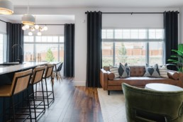 Living area with wire and wood barstools, leather couches with dark hardwood floor and grey curtains. The Lusitano Showhome in Jensen Lakes by Pacesetter Homes in St. Albert