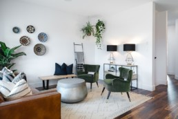 Living room with dark green velvet chairs and brown leather couch, white walls and black lamps. Showhome in Jensen Lakes St. Albert by Pacesetter Homes