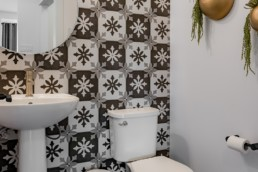 Bathroom with geometric wallpaper and stand alone sink. Showhome in St. Albert